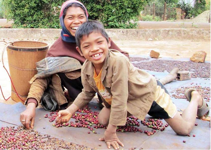 chị H'Kinie cùng con trai lớp 4 bên cạnh hạt cà phê lép mới đi mót về